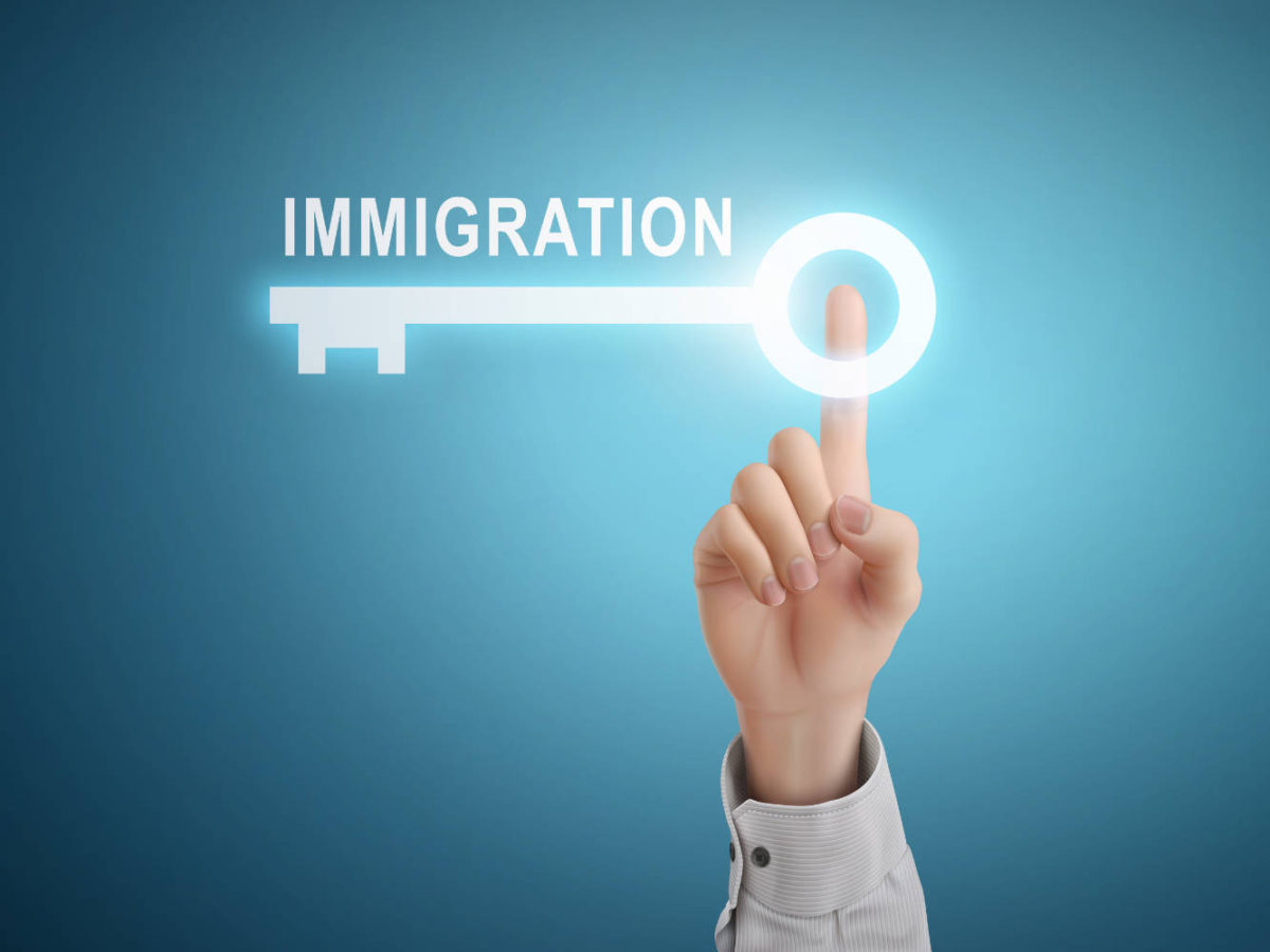 male hand pressing immigration key button over blue abstract background
